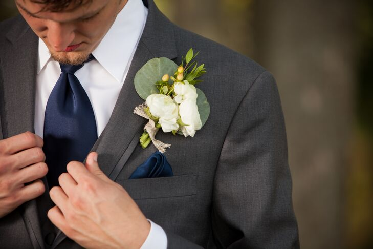 The groom had an ivory ranunculus boutonniere accented with yellow hypericum berries.