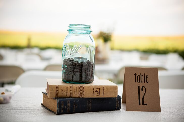 A mason jar filled with coffee beans and a lit candle sat on top of two antique books purchased at a thrift store. Next to the arrangement was a simple brown cardboard paper table number.