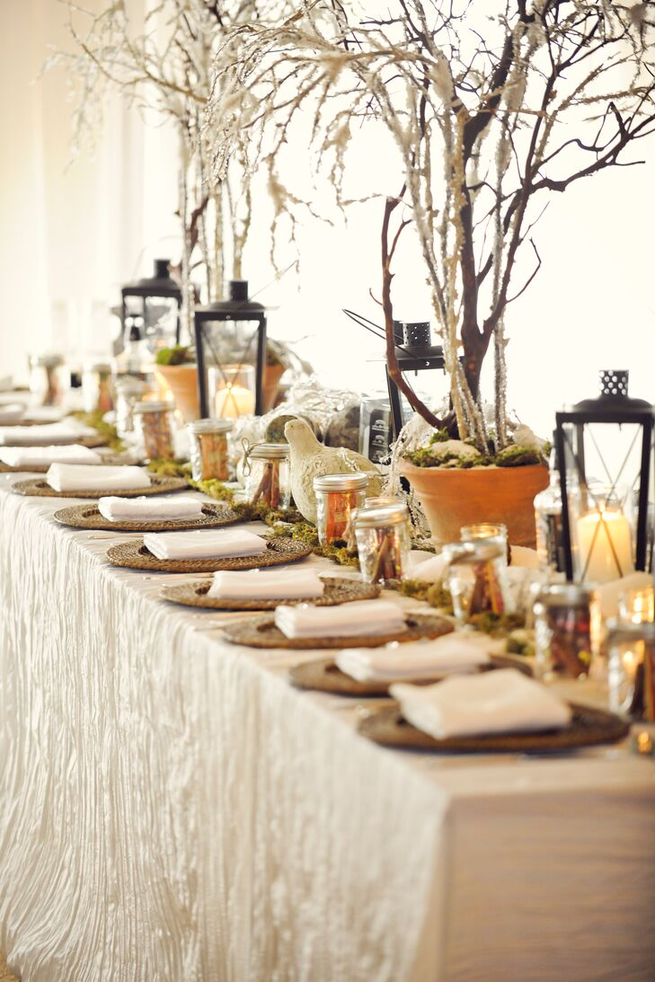 Lanterns, faux birds and tall branches topped tables.