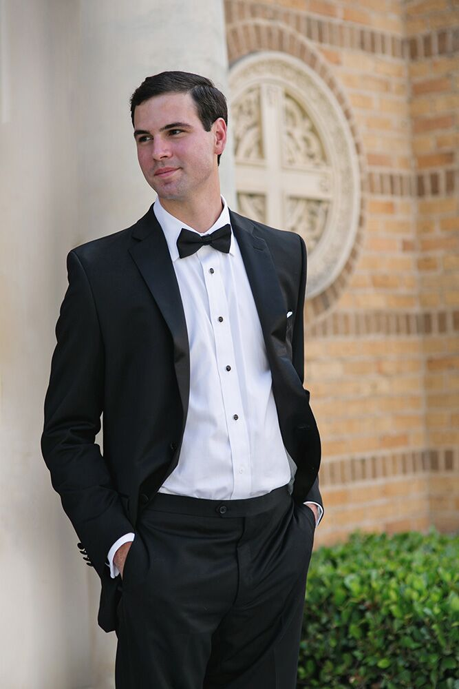 The groom wore a black Calvin Klein tuxedo with no cummerbund and a black bow tie.