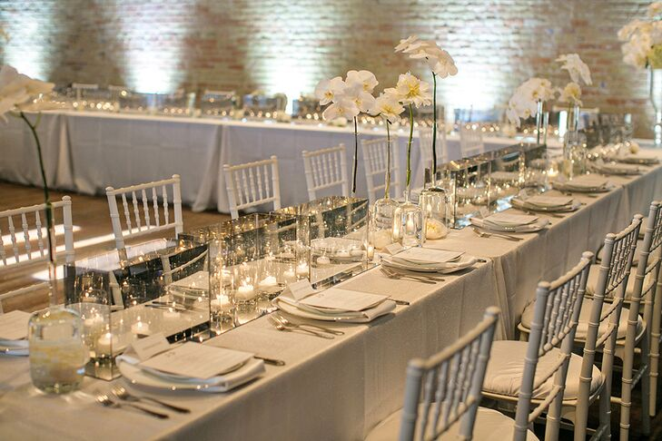 Brazos Hall hosted the reception and set up a U-shaped Head Table for 43 covered in white luxury linens, a mirrored runner, and chic infinity mirror boxes with large open white peony blooms (with orchid and hydrangea varieties) in between to soften the design.