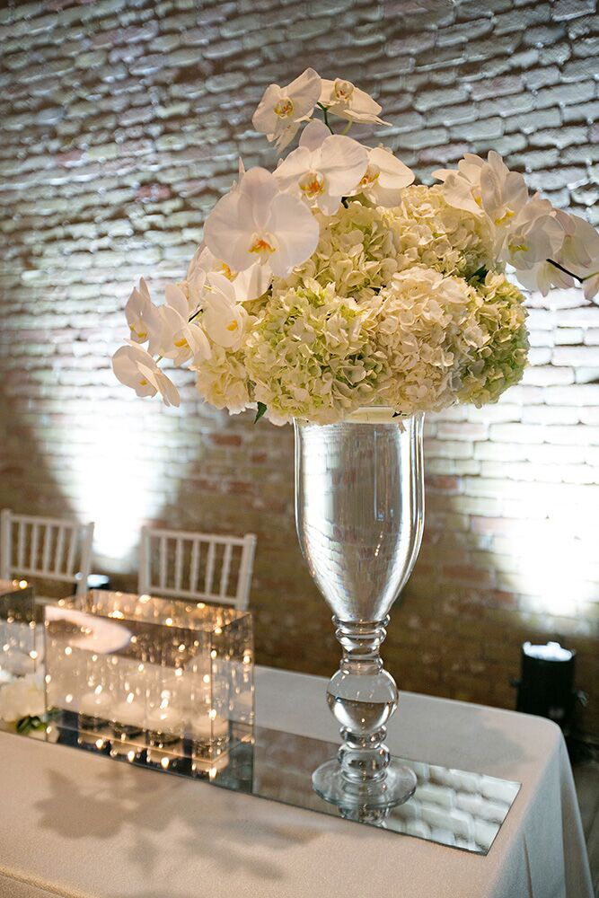 Fluffy arrangements of white orchids and hydrangeas lightened the reception tablescapes.