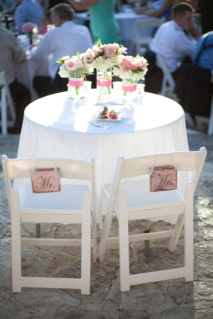 "Kate and Frank's classic white sweetheart table featured three simple glass vases with a blend of white and blush hydrangeas, roses and peonies. Rustic light pink ""Mr. & Mrs."" signs hung on the back of their chairs."