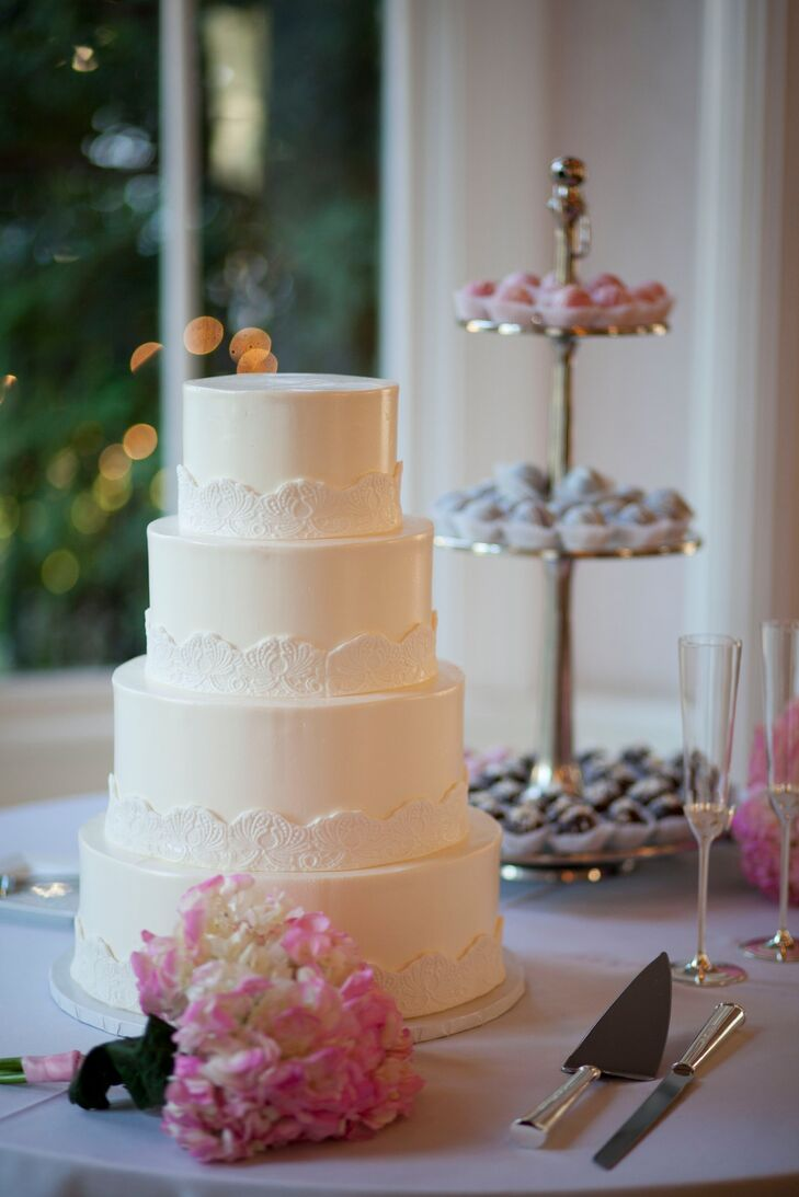 Kate and Frank had a classic simple ivory four-tier wedding cake with a white lace border.