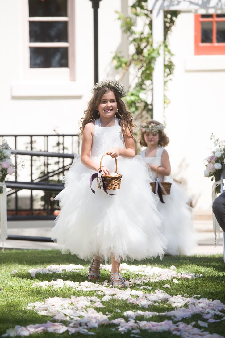 The flower girls wore white dresses with lace detailing on the top (to go with Lidia's stunning lace sheath dress) and full, tulle tutu skirts. They completed their look with baby's breath flower crowns and threw blush rose petals down the aisle.