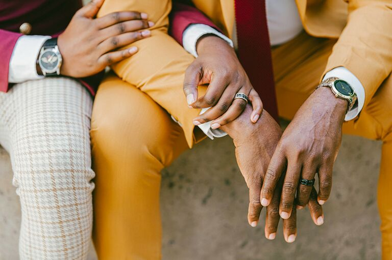 Close up of engagement rings on couple's hands