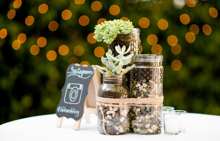 A mini chalkboard easel placed among glass jars of pebbles and succulents shared the couple's Instagram hashtag.