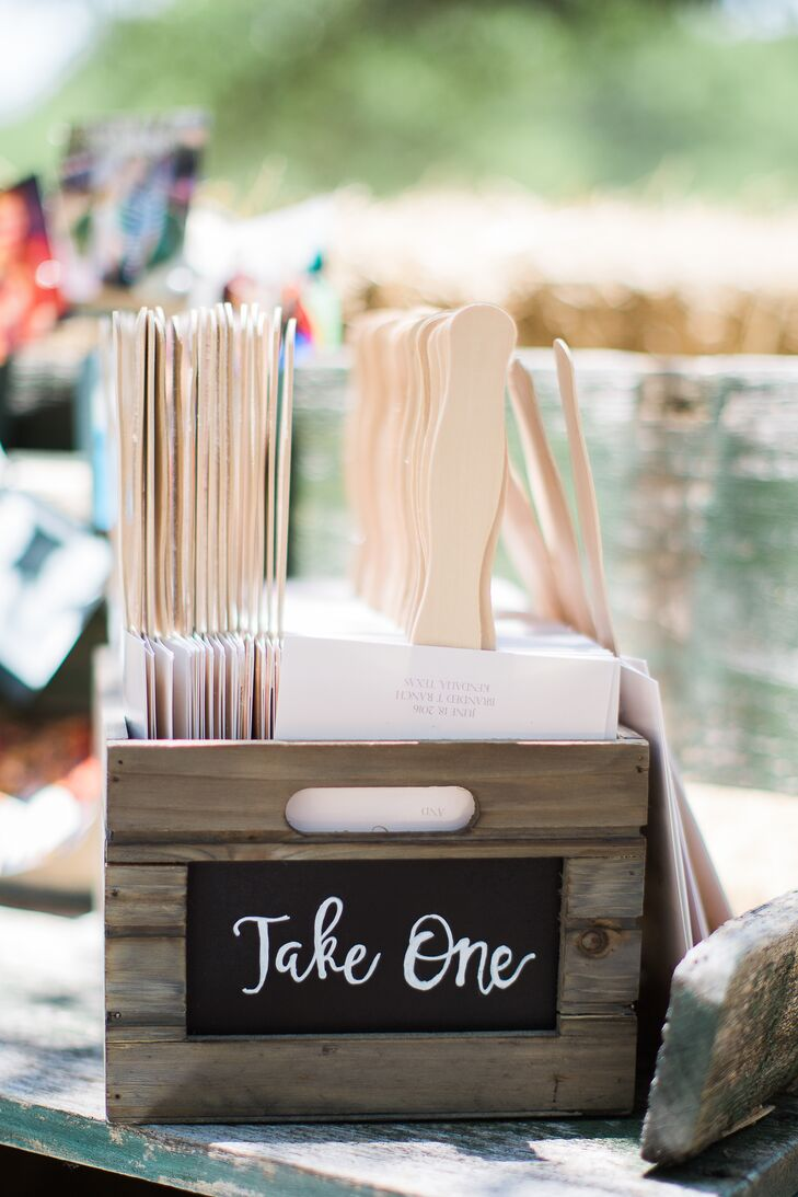 """Fan favors were displayed in a wooden crate, decorated with a simple """"take one"""" chalkboard message sign."""
