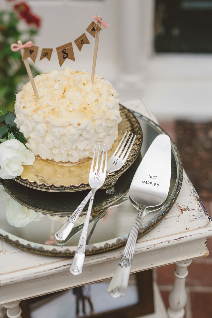 """The small white cake had a rosette pattern and a flag topper that displayed Christy and Brady's monogram. They served the cake with a silver serving set, which had engraved forks that read """"I Do"""" and """"Me too"""", positioned next to the knife that read """"Just Married."""""""