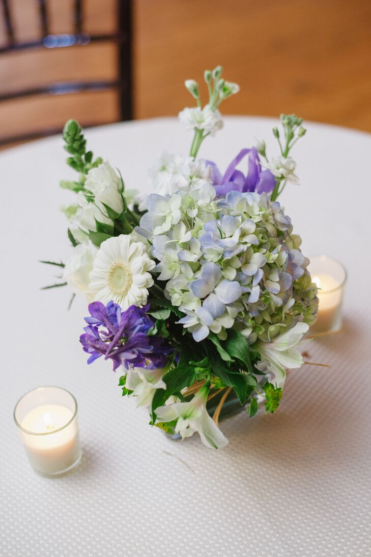 Playing off the winter season, Kim and Justin chose a cool color palette of white, blue and purple, which balanced the warm tones of the rustic barn's interior. Floral Arts Flowers incorporated the cool colors into all of the centerpieces, creating fresh bunches of hydrangeas, stock, gerbera daisies and delphiniums that popped against the tables' crisp white table linens.