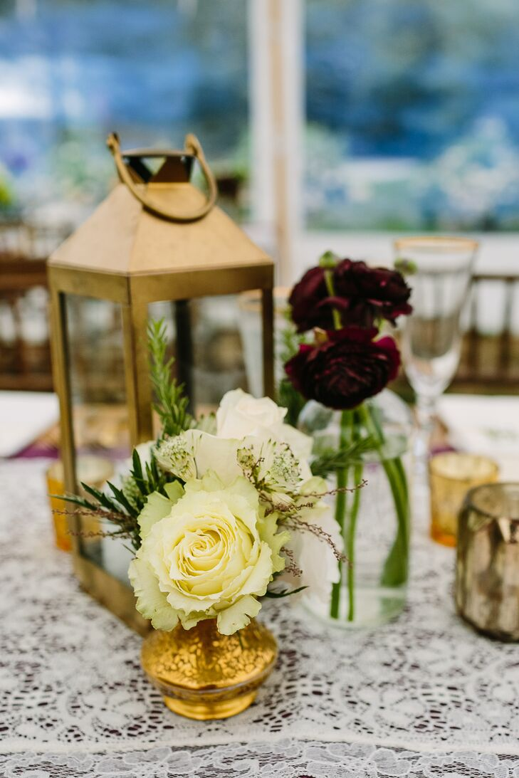 Small vases of dark red and white roses stood alongside small candle votives and a gold lantern for the elegant centerpieces.