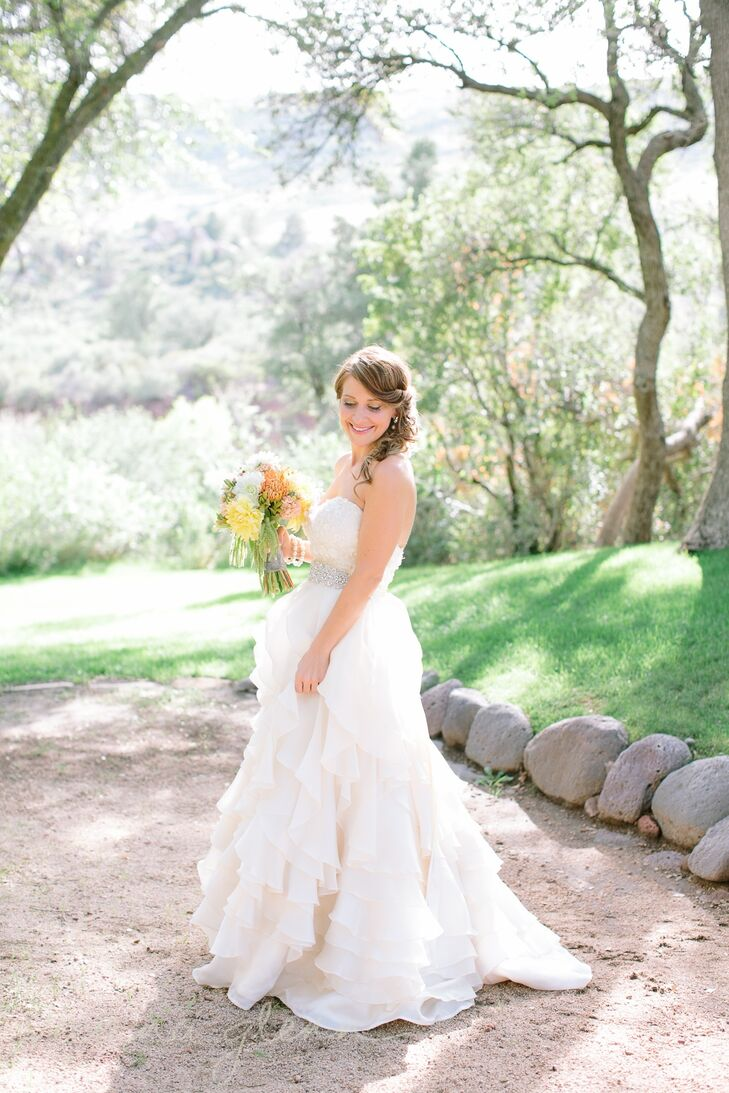 Jennifer's dress was a stunning creation by Jim Helm. The A-line gown had an embellished bodice, accented by a crystal-embellished belt, and layers of cascading ruffles that came together to create a romantic look with a hint of glam.