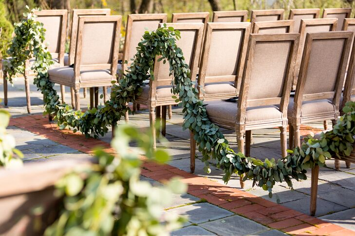 To play up the garden's lush natural setting overlooking a valley surrounded by tall, majestic trees, the couple lined the aisle with long, lush eucalyptus garlands.