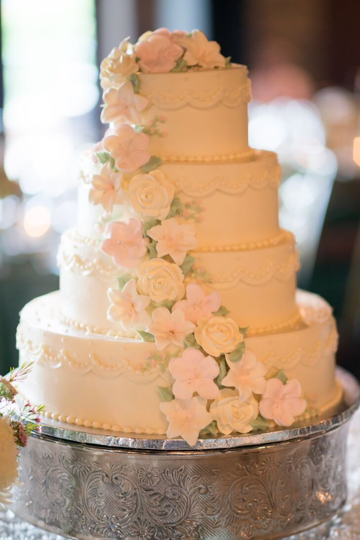The ivory wedding cake was flavored red velvet with buttercream filling. It was decorated with piping and cascading blush and ivory cake flowers.
