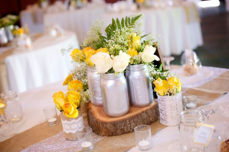 "Mason jars were painted and filled with ivory and yellow flowers, such as roses, peonies and baby's breath. The flower arrangements were on a slab of wood and served as table centerpieces. ""I'm definitely a DIY kind of girl, and I had a whole year to plan my wedding, with the help of others of course,"" says Vanessa. ""I did a lot of thrift and antique shopping for my decor. Everything was personally made by my family and I.""  rn"