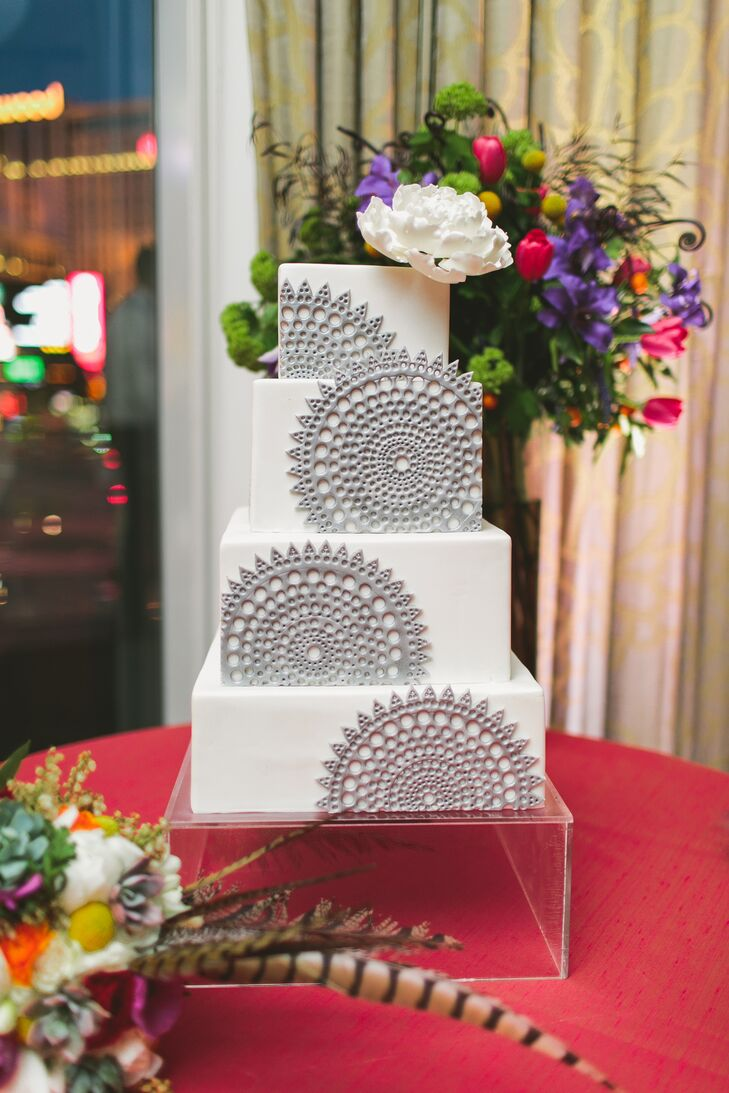 The four-tier white wedding cake had vintage-inspired gray sunburst designs decorating every layer of the dessert. The cake had flavors of vanilla cake with passion fruit filling and chocolate sponge with peanut butter and jelly.