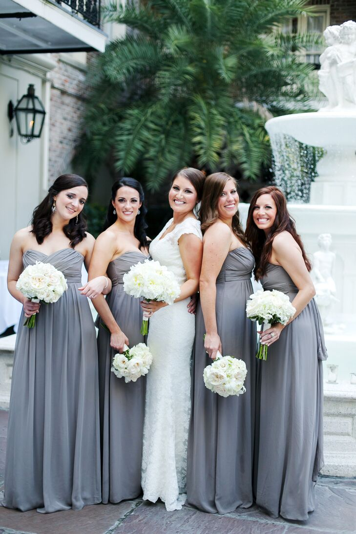 The bridesmaids wore gray strapless sweetheart neckline dresses and carried all-white bouquets to match the bride's arrangement.