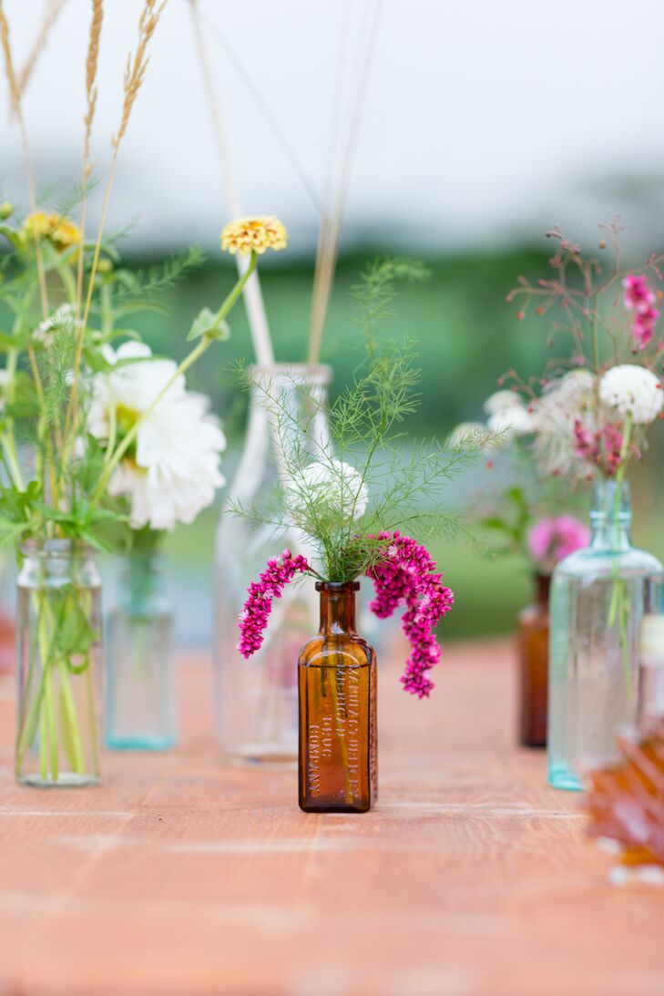 Inspired by the farm's natural setting, Molly and Alex went for a rustic, fall aesthetic when it came to the decor. The pair filled the reception tent with natural wood tables, which they topped with clusters of antique medicine and milk bottles Molly's uncle had collected in forests throughout New Hampshire and Vermont. Each bottle was filled with a vibrant mix of colorful wildflowers, bringing a dash of vibrancy and energy to the tabletops.