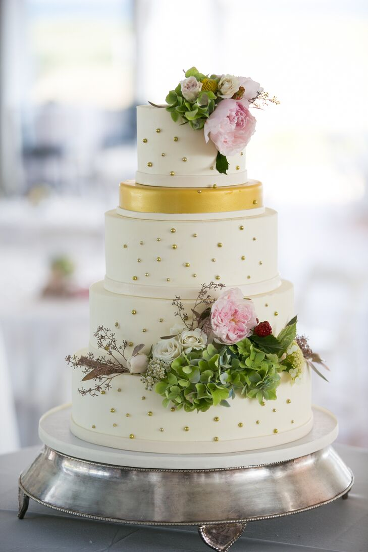 The wedding cake was iced in white and featured lemon cake with vanilla bean and raspberry buttercream frosting. One layer of the cake was iced in gold, while the other tiers had gold accents. Fresh, organic florals highlighted the dessert.