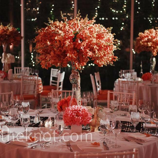 Orange chair cushions and tall sprays of orange orchids on top of the white linen tables added serious color to the vibrant space.