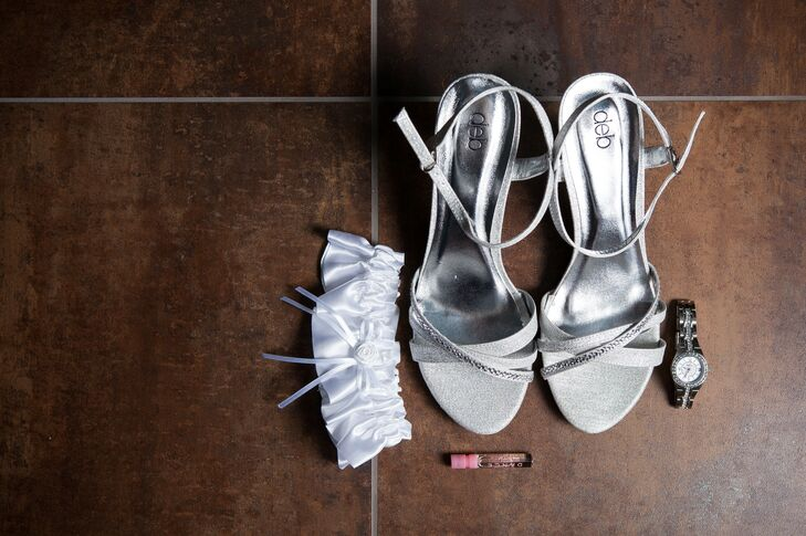 The bride wore silver shoes on the wedding day, which were positioned next to a white garder, small perfume bottle and silver watch.