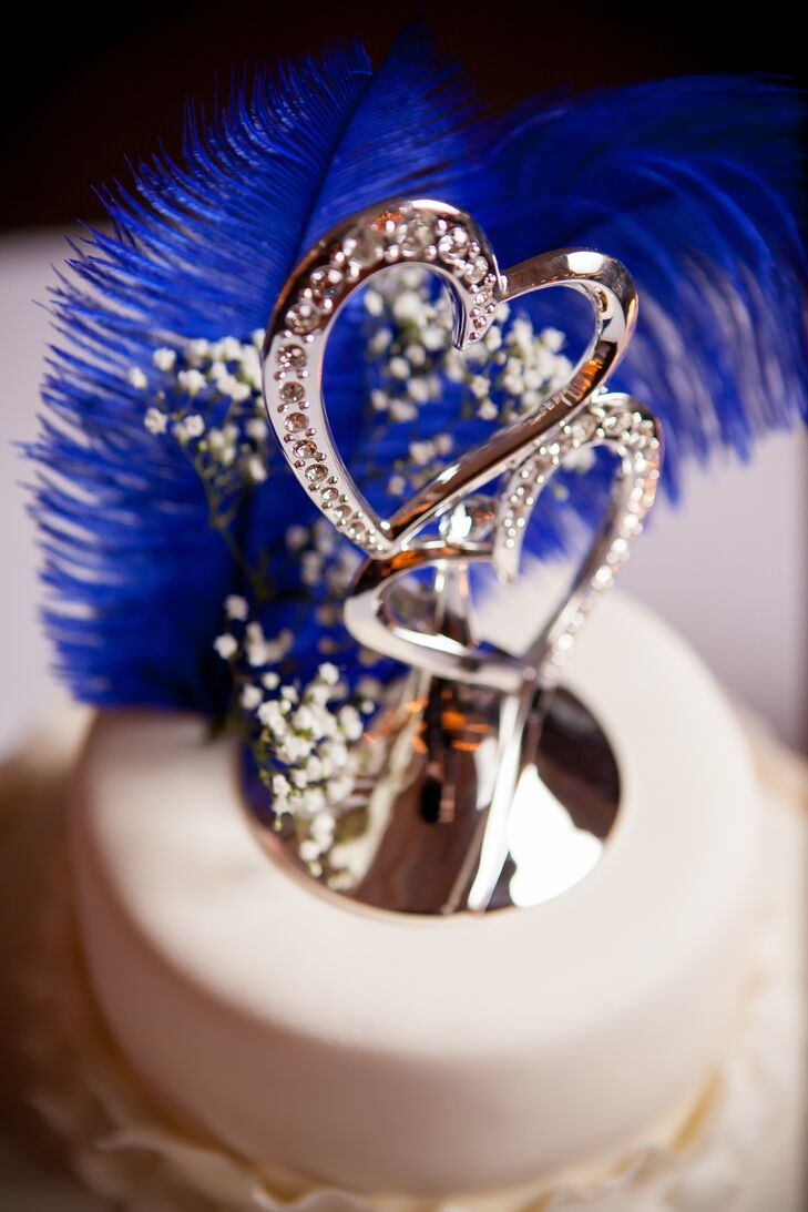 Two silver hearts accented with blue feathers and baby's breath served as the cake topper on the wedding cake.