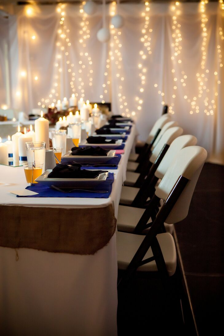 Reception tables were dressed in white, royal blue and gold linens with lit candle centerpieces.
