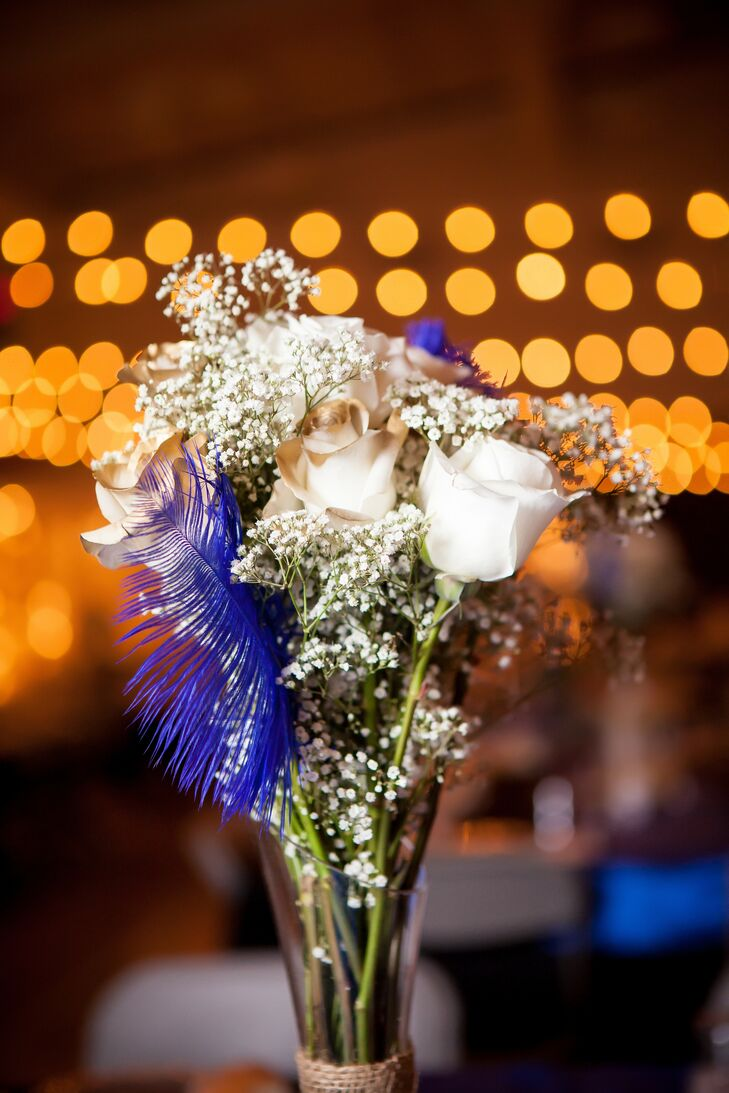 Gold and white roses were accented with blue feathers and baby's breath, mixed together and placed at reception tables as centerpieces.