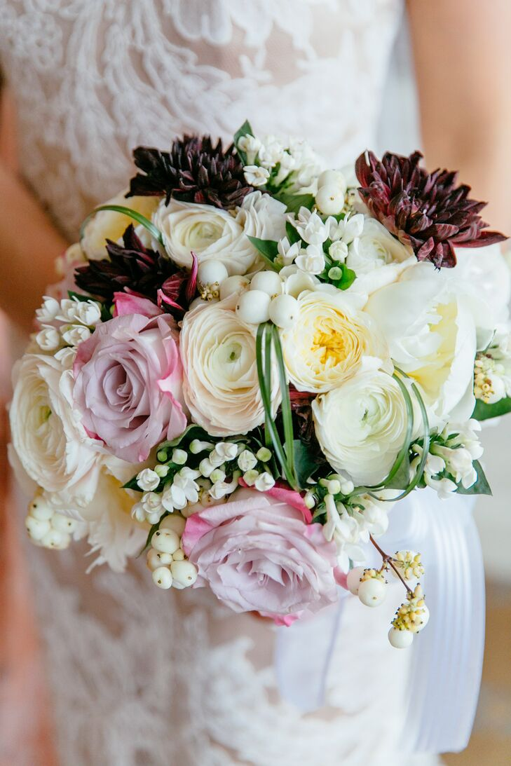 Jenna's bouquet was lush with a little edge. Burgundy dahlias stood out against the arrangement's pink roses, white ranunculus, yellow garden roses, white peonies, white hypericum and waxflowers. Her great-grandmother's necklace was also woven into the bouquet by Michael George, their florist.