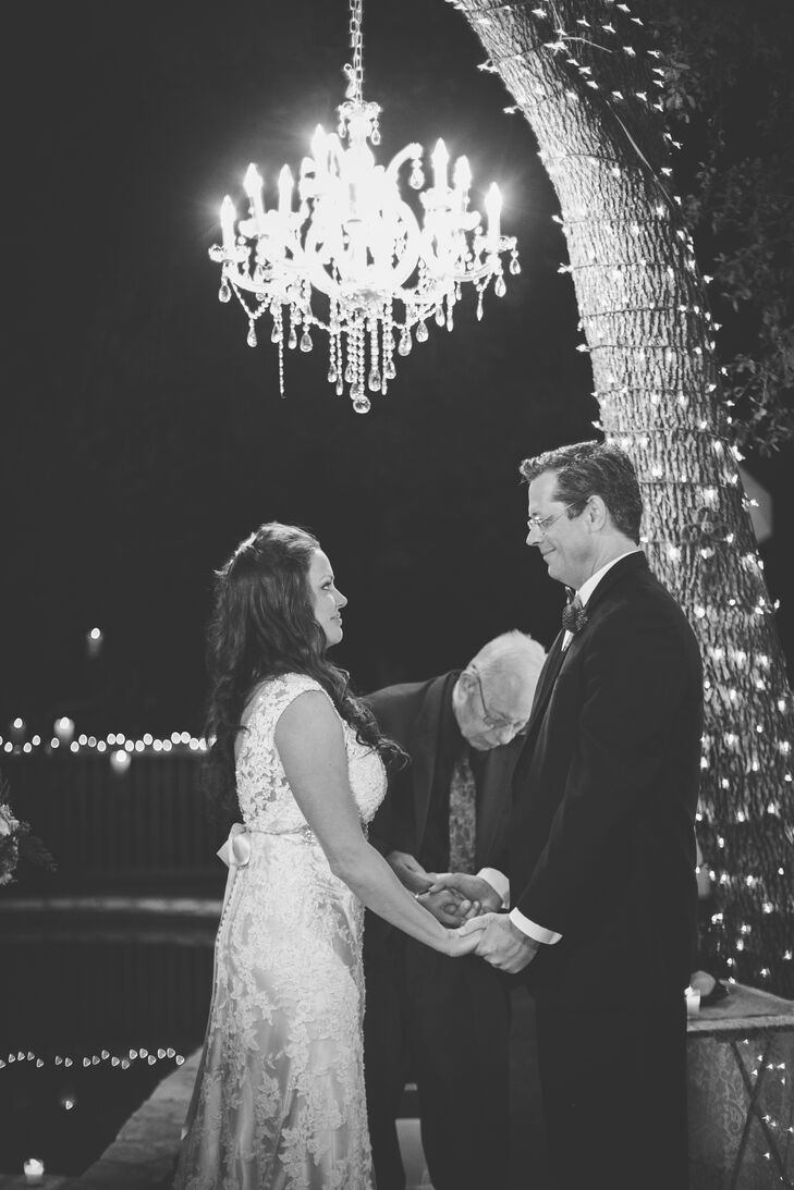 """The couple got married in Roxanne's backyard underneath a towering oak tree wrapped in Christmas lights, with a crystal chandelier hanging over where the couple exchanged their vows. """"Kevin loves that we can always look in our backyard after our wedding and remember the special day,"""" says Roxanne."""
