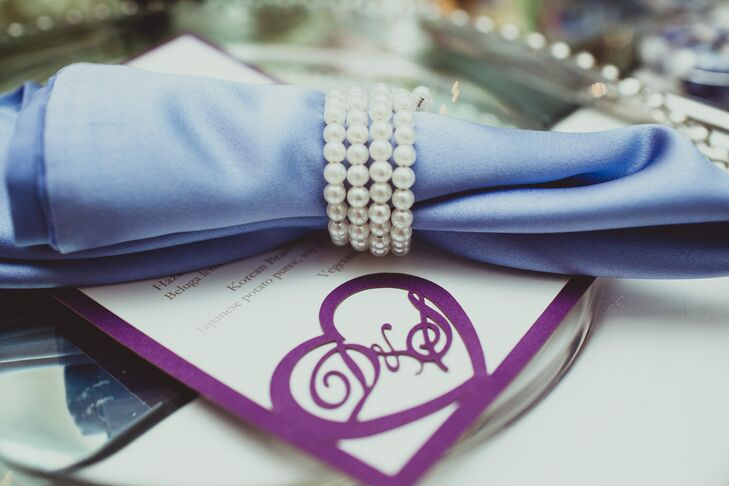 The white menu card was accented with a purple heart design that displayed the couple's initials, which matched the border of the stationery. A napkin in a different shade of purple was held together by a pearl ring and placed on top of the menu.