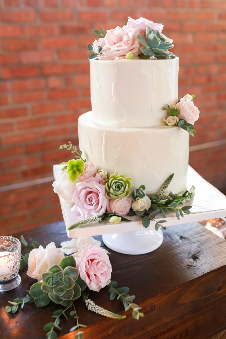 Sweet Cheeks bakery created Andrea and Corey's simple two-tier cake, which tied into the floral theme with a few fresh roses and sprigs of greenery.
