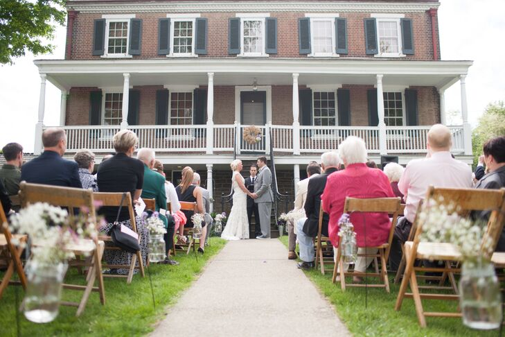 Sara and Josh were married outdoors in a ceremony by the house at West Overton Village. The aisle was lined with mason jars of baby's breath hanging from shepherd hooks.