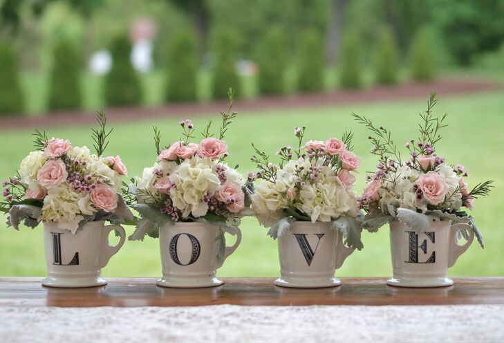Broad Brook Gardens, the couple's florist, added to their shabby chic theme with a few touches of Laura's favorite flowers, hydrangeas and peonies. Each mug was filled with white hydrangeas, pink roses, dusty miller and stock flowers. More low arrangements were placed throughout the reception. Silver breakaway vases and clear-glass mason jars were filled with white roses and white peonies.