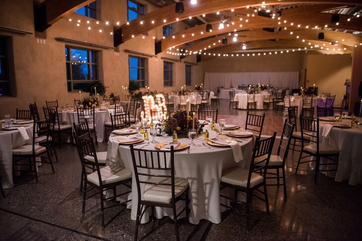 At the indoor, on-site reception at Springs Preserve in Las Vegas, Nevada, candelabras were placed around the floral centerpieces to add ambience. Wooden, free-standing numbers were placed on each table for guests to find their seats.