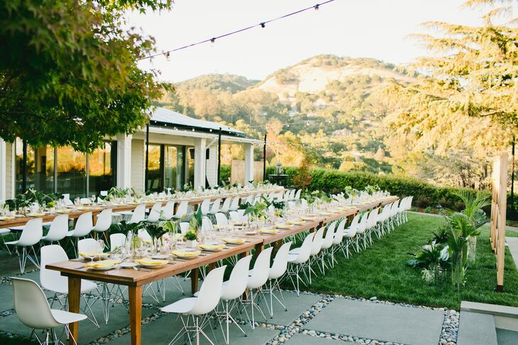 At the reception, long wooden banquet tables used white chairs from the ceremony as seating. Tables were topped with clear vases of fresh fernlike greens. Yellow napkins added a pop of color.