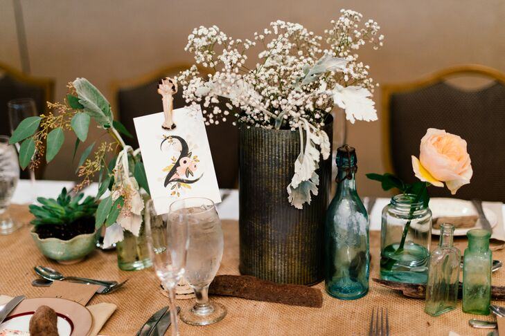 To infuse the Omni's interiors with a dash of the ceremony's beachy, carefree vibe, the couple used blue antique bottles, distressed tin vases, driftwood and burlap linens to dress the reception tables. Baby's breath, succulents, peach-colored garden roses and greenery were woven throughout for a romantic touch.