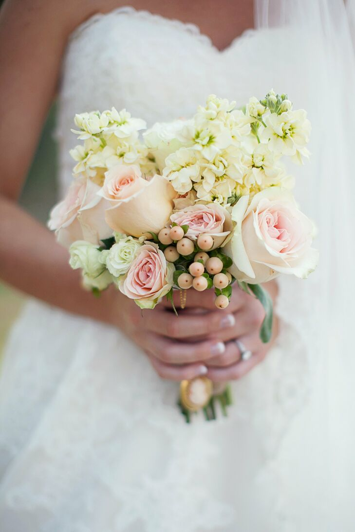 Laura carried a small bouquet of ivory and pale pink flowers, which included roses, snapdragons, and hypernicum berries.