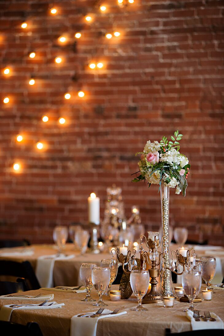 """While Alexis and Andrew were originally hoping to wed in a barn, the logistics proved to be more complicated than they imagined. Luckily, Paola Town Square had the quaint, shabby-chic feel they were after with its exposed brick walls, elegant chandeliers and vintage furnishings. """"When I was explaining my vision, Michelle grasped it immediately and she had just about every little piece of decor I could have possibly wanted—gold candelabras, chalkboards, mercury glass and more,"""" Alexis says."""