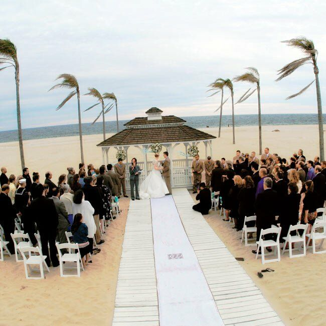 The ceremony took place in front of a gazebo on the beach, with palm trees swaying in the background.