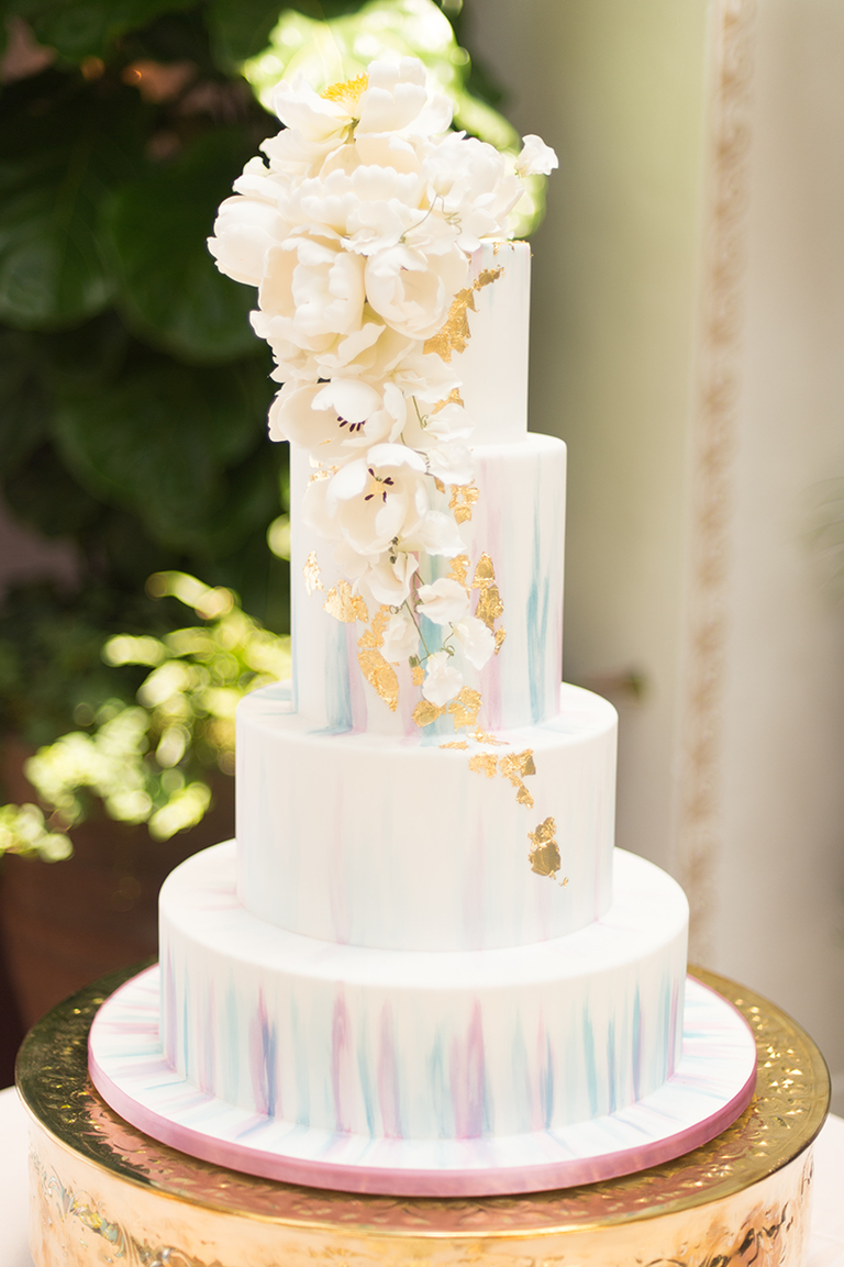 White wedding cake with watercolor designs and gold leafing