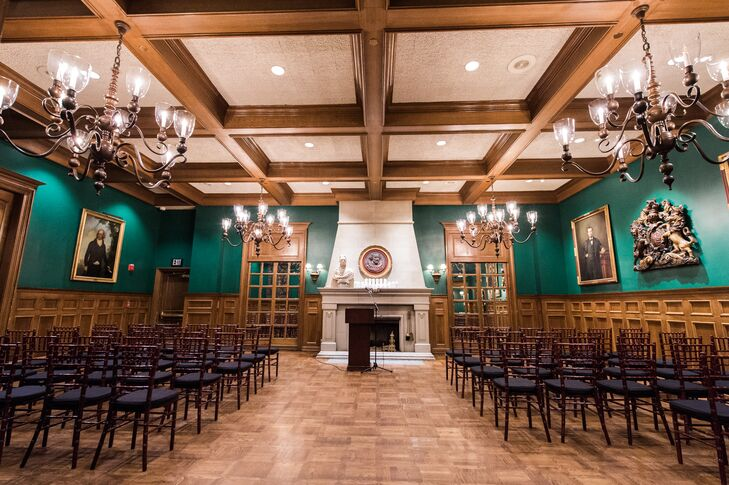 """Jon and Andrew exchanged vows in a short ceremony held in front of the Oak Room's fireplace. """"The space was decorated with white rose petals along the aisle and white pillar candles on the hearth of the fireplace,"""" Jon says."""