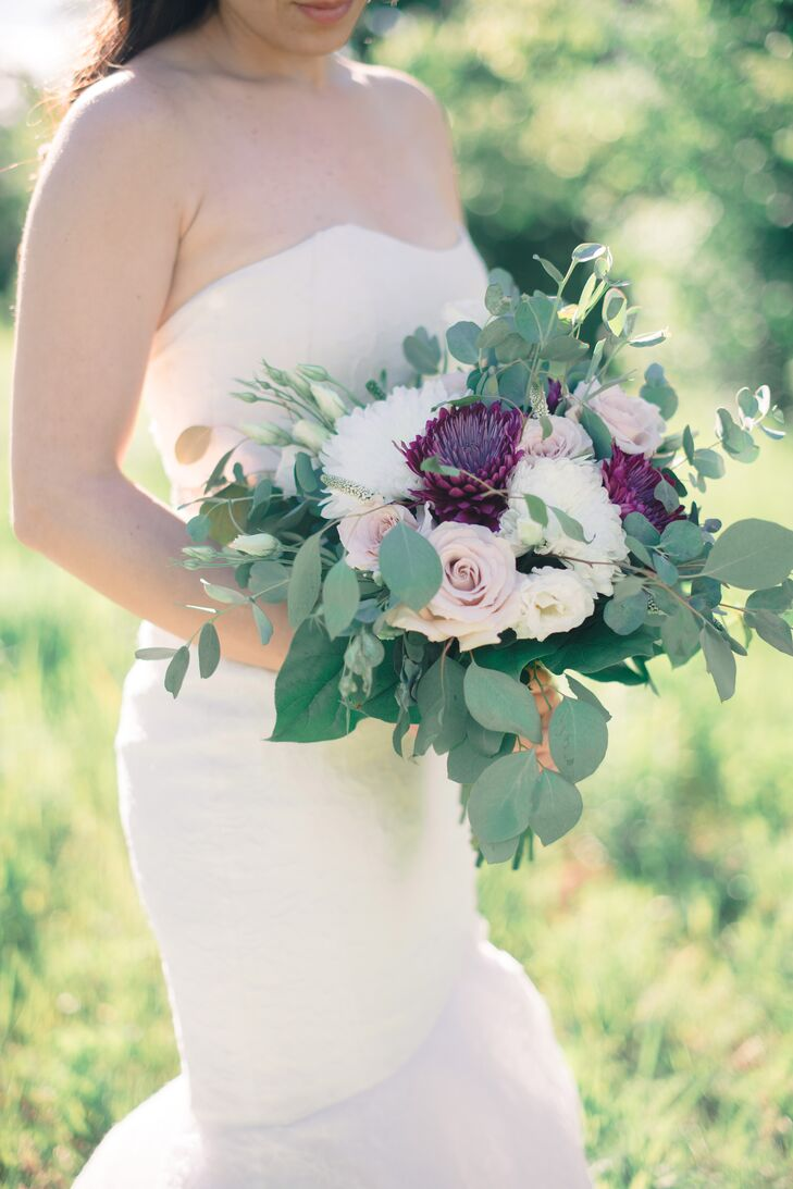 Trillium Floral Designs amped up the drama of Nancy's down-the-aisle ensemble with a textured bouquet of eucalyptus, roses and deep purple chrysanthemums.