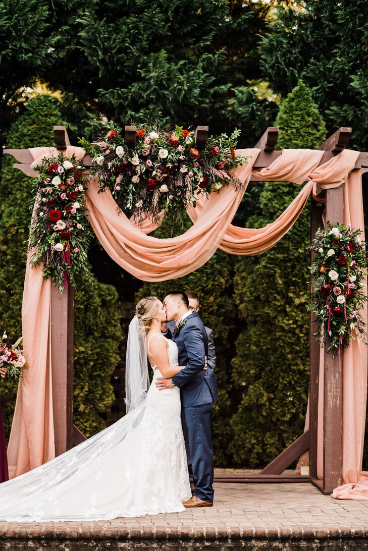 Couple Under Wedding Arch with Pink Draping, Roses and Greenery