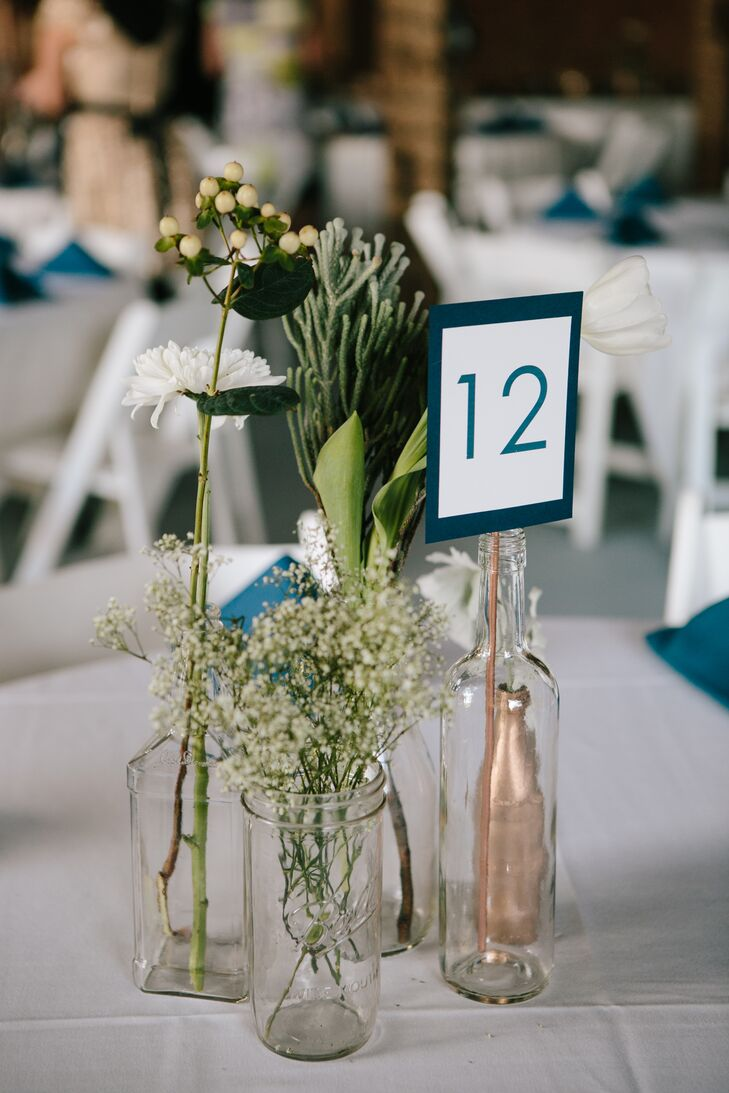 The simple centerpieces were made up of clear and rose gold painted bottles with single-stem flowers.