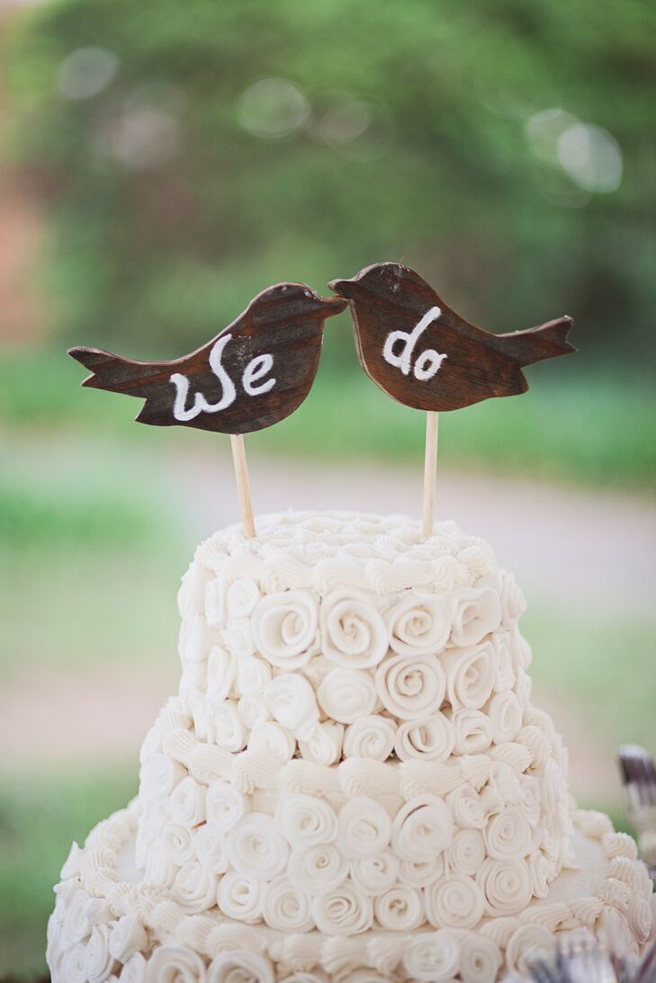 """Paula Little made Emily and Alex's cake for dessert. It was entirely decorated with buttercream rosettes for a romantic touch. The topper included two little wooden birds that said """"We do"""" in white paint."""