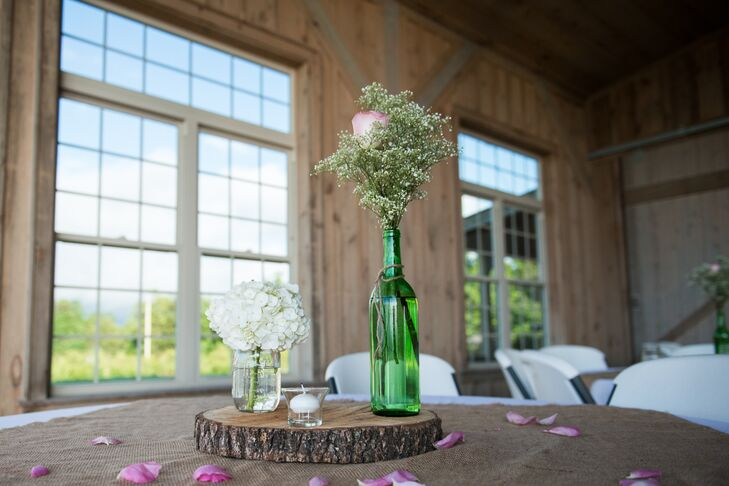 "Rachel and Alex reflected their minimalist rustic theme through their simple centerpieces. ""We had single roses in green wine bottles, tree stump centerpieces with burlap and single cut hydrangeas in mason jars,"" says Rachel. ""I wanted it to reflect our Southern roots, but still feel outdoorsy and casual."""