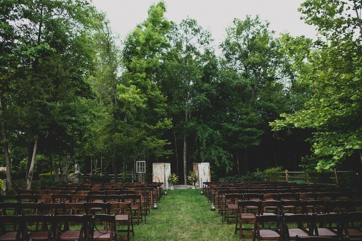 The ceremony took place in Kelsey's backyard under and they decorated the space with dark wooden chairs. At the end of every other aisle were shepherd hooks with lanterns attached at the end that had candles inside of them. Two vintage old white doors were at the end of the aisle that framed where we got married. We also hung a large chandelier between the two doors. We had two large pots of flowers on the ends of the doors that became the entryway for the walkway that my groom, officiate, and best man entered from behind.