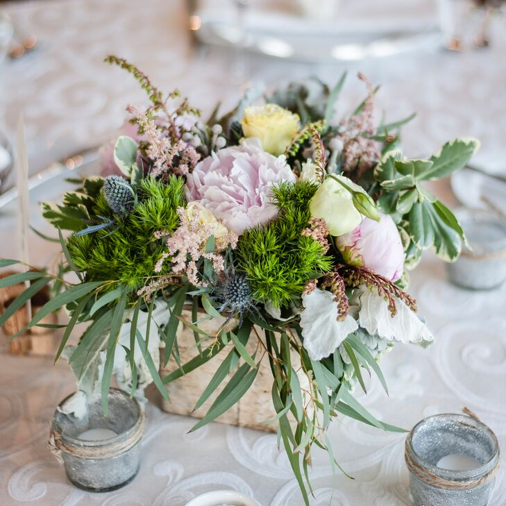The centerpieces were small arrangements of pastel peonies and roses offset by blue thistle and assorted greenery.