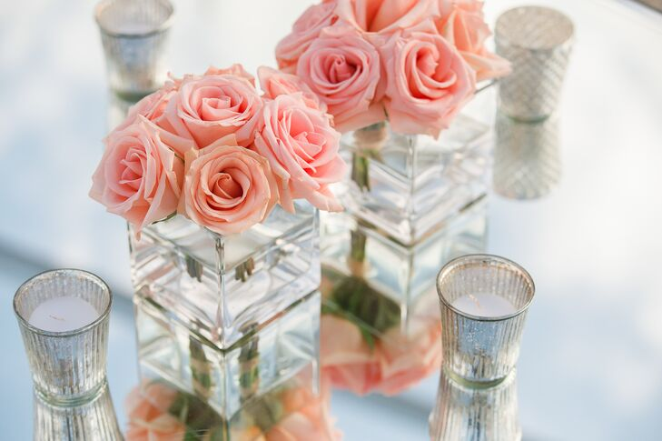 Dining tables at the reception had modern square glass vases with pink roses.